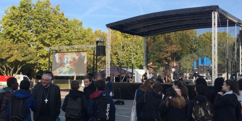 Monseigneur Santier salue les jeunes, sur un fond de pop louange