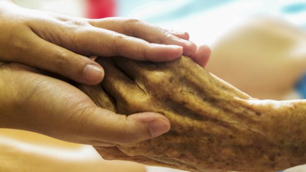 Soignant qui tient la main d'une personne âgée